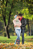 Loving couple kissing in the park in autumn. A loving couple kissing in the park in autumn Stock Photo