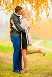 Loving couple kissing in park. A loving couple kissing in autumn park Stock Photo