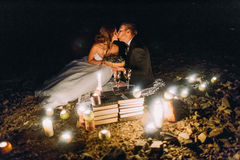 Loving couple kissing on romantic dinner with candles and cake  at beach, coast against wonderful night Royalty Free Stock Image