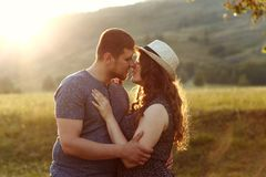 Loving couple kissing at sunset in nature, honeymoon, mountains, back light, soft light, emotions, happiness, royalty free stock images