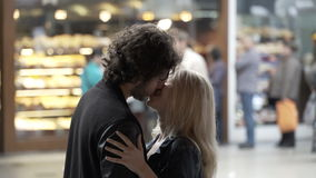 Loving couple in kissing and talking in public on a street with people in background. Young loving couple in kissing and talking in public on a street with stock footage