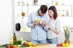 Loving couple in kitchen makes healthy juice of fresh orange by hand. Little juice Royalty Free Stock Photos
