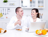 Loving couple with laptop in the kitchen Royalty Free Stock Photos