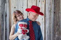 A loving couple laughing and embracing. Horizontal image of women standing behind her men who is wearing cowboy hat and red tie with little white hearts royalty free stock images