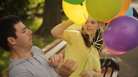 Loving couple laughing in the park with balloons stock video
