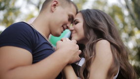 Loving couple laughing in the park with balloons stock footage