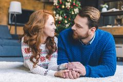 Loving couple holding hands on christmas stock photo