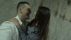 Loving couple in loft nightclub. Happy young couple in love posing cheerfully and embracing in grungy concrete loft. A guy and a girl do selfie on the background stock video footage