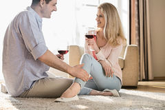 Loving couple looking at each other while drinking red wine at home Stock Photography