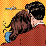Loving couple looking at a plane taking off in the royalty free illustration