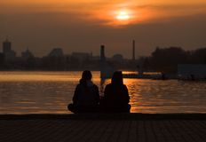 Loving couple looking at the sun. stock photos