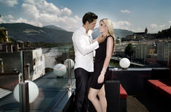 Loving Couple. Young happy couple is standing and laughing on a terrace Stock Photography