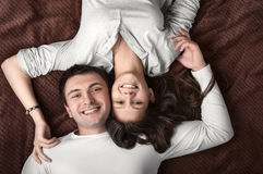 Loving couple lying on bed Stock Photos