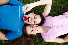 Loving couple lying on a grass stock photos