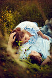 Loving couple lying in the grass in a summer field. Royalty Free Stock Photo