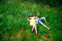 Loving couple lying on green grass in summer Royalty Free Stock Image