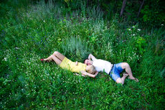 Loving couple lying on green grass Royalty Free Stock Images