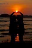 Loving couple make heart shape on beach with the sun set Stock Photo