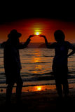 Loving couple make heart shape on beach with the sun set Stock Image