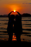Loving couple make heart shape on beach with the sun set Royalty Free Stock Photography