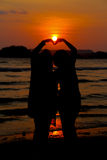 Loving couple make heart shape on beach with the sun set Royalty Free Stock Photos