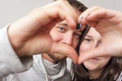 A loving couple makes a heart sign from their palms. Loving couple men and women holding hands in heart silhouette Royalty Free Stock Photo