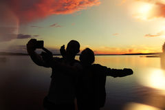 Loving couple makes selfie at sunset near the lake. Lens flare effect. A loving couple makes selfie at sunset near the lake. Lens flare effect Stock Image
