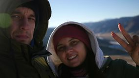 A loving couple makes selfie on top of the mountain, with a gesture of victory on the fingers. slow motion, 1920x1080. A loving couple makes selfie on top of the stock video