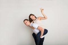 Loving couple, man piggybacking girlfriend. Loving couple piggybacking. Happy young men with his girlfriend posing for camera, having fun together Stock Photography