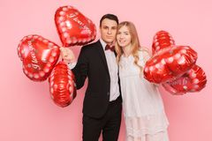 A loving couple, a man and a woman, holding heart-shaped balloons, in a studio on a pink background, concept for Valentine`s Day