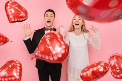 A couple in love, a man and a woman, holding balloons in the shape of a heart on a pink background, enjoy Valentine`s day