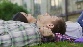 Loving couple of mixed-race teens lying on lawn, enjoying date. First love stock video