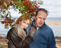 Loving couple at a mountain ash bush.Portrait in a sunny day Stock Images