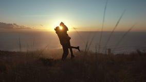 Loving couple on mountain peak at sunset stock footage