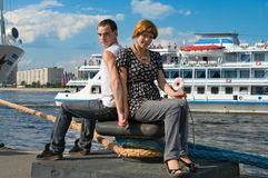 Loving couple near the cruise lainers. Teenagers: girl and fellow are in harbor Stock Images