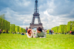 Loving couple near the Eiffel Tower in Paris. Loving couple lying on the grass on the Champ de Mars in Paris with the Eiffel Tower in the Background Royalty Free Stock Image