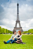 Loving couple near the Eiffel Tower in Paris. Loving couple lying on the grass on the Champ de Mars in Paris with the Eiffel Tower in the Background Stock Photography