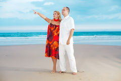 Loving couple near the ocean. Woman showing something by finger near the ocean Royalty Free Stock Photography