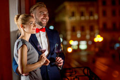 Loving couple on the night city background. Loving couple with wine glasses embracing on the balcony on the night city background Stock Photos