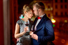 Loving couple on the night city background. Loving couple with wine glasses embracing on the balcony on the night city background Stock Photo