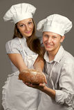 Loving couple offer round loaf Stock Images