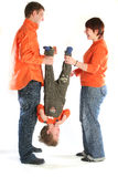 Loving couple in orange clothes holding their child Stock Photo