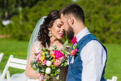 Loving couple outdoors with wedding bouquet. Stock Photography