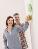 Loving couple painting a room. Smiling loving couple painting a room, they are holding a paint roller together Royalty Free Stock Images
