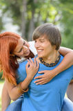 Loving couple piggyback hugging in sunny park Royalty Free Stock Photo