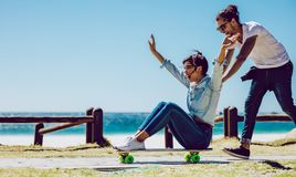 Loving couple playing on skateboard near the beach. Loving couple playing on the skateboard outdoor near the beach. Happy women sitting on skateboard with Royalty Free Stock Images
