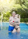 Loving couple in the pool in a garden with tropical trees. The man embraces the woman Stock Photo