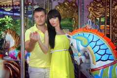 Loving couple posing with carousel horses Stock Images