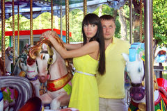 Loving couple posing with carousel horses Stock Photo