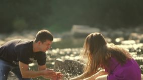 Loving Couple Pours Water on a Mountain River. Sun reflections in the camera lens stock video